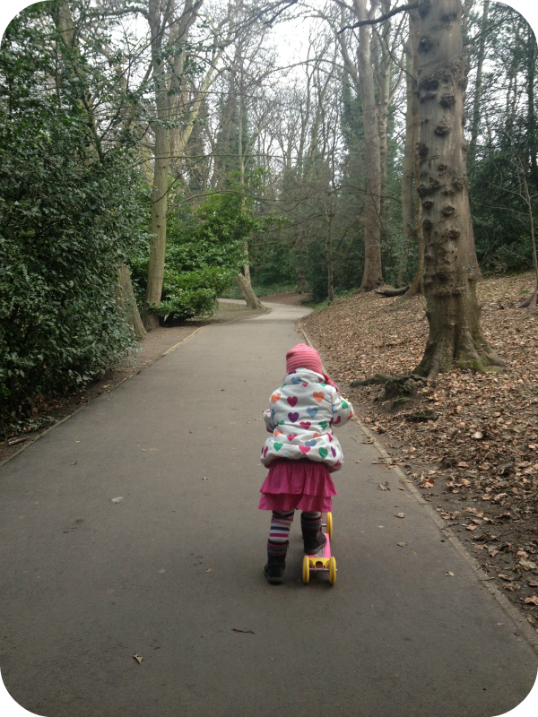 Child on scooter in park