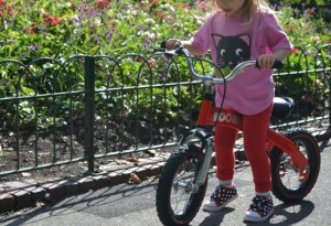 Toddler girl on balance bike in the park